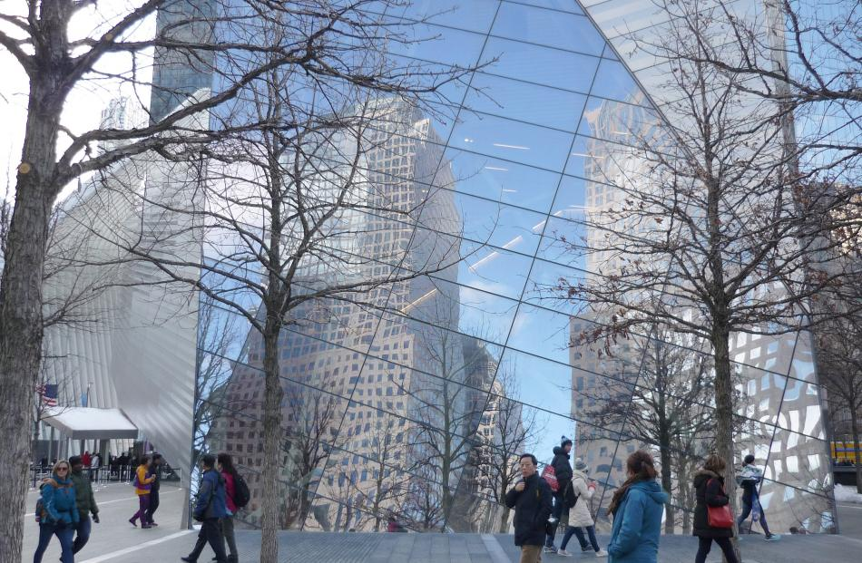 Buildings are reflected on the glass exterior walls of the 9/11 Memorial Museum.