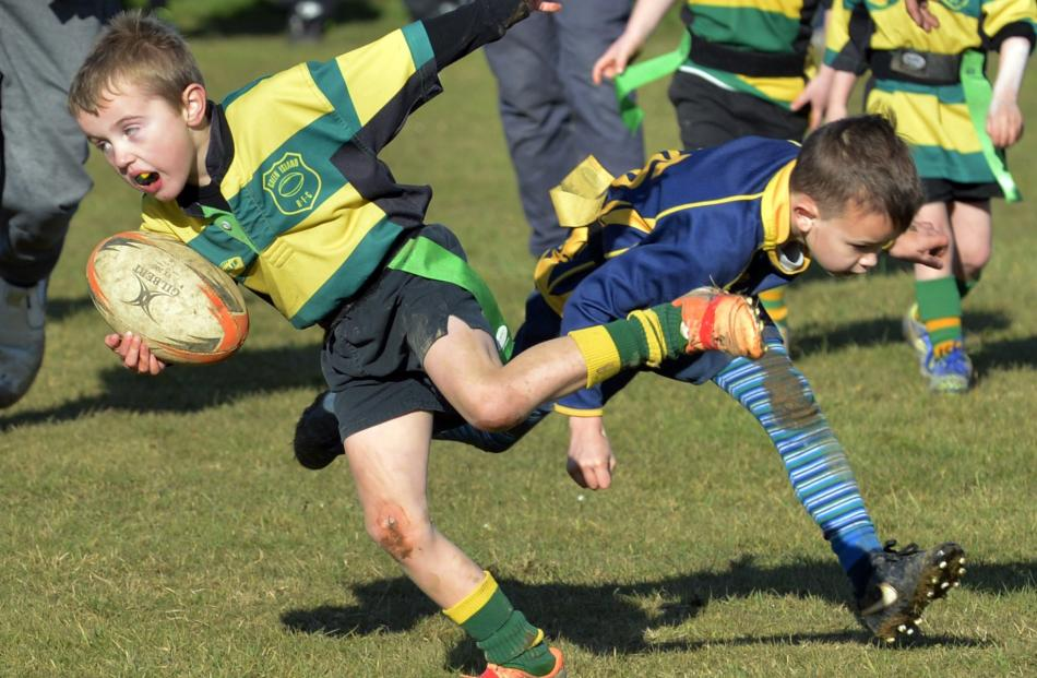 Mason Bond (6), of Green Island Black (above left), dodges the tackle of Robbie McPherson (6), of Dunedin Mako Sharks, in an under-7 division match.