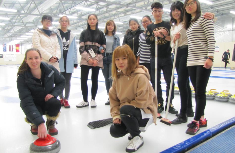 New Zealand under-19 curling team member Jessica Smith (19, front left), of Naseby, shows members of a visiting group from the Shanghai Institute of Technology the finer points of curling after the group's session at the Naseby Indoor Curling Rink on Satu