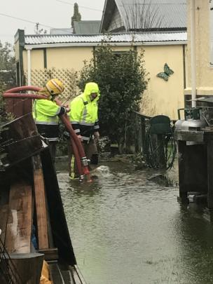 Firefighters work to pump water from a flooded Argyle St house in Mosgiel. Photo: Margot Taylor