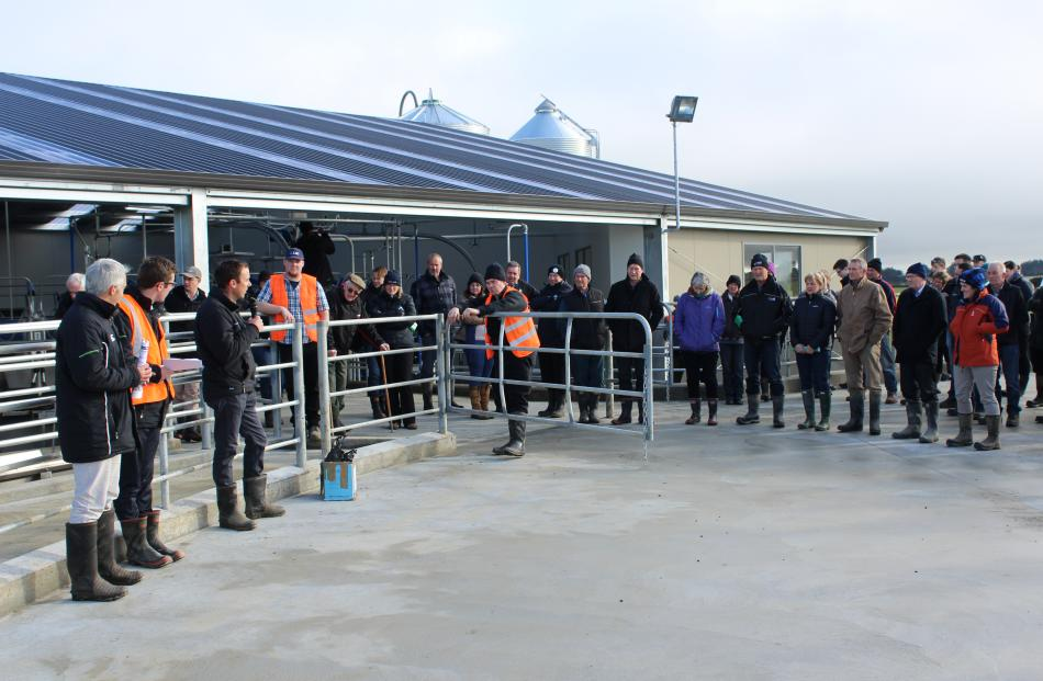 Southland Farm Services operations manager Mark McMillan, talks to visitors at the Southern Dairy Hub with DairyNZ consulting officer Nathan Nelson (second from left) and DairyNZ scientist Paul Edwards (left) about the milking shed at the hub.