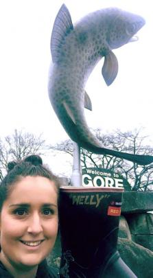 Megan McGregor holds Welly in front of Gore's trout statue. Photos: Supplied