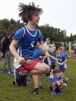 Quinn Byers (11), of Macandrew Bay School, shows some energy in his warm-up before the years 5...