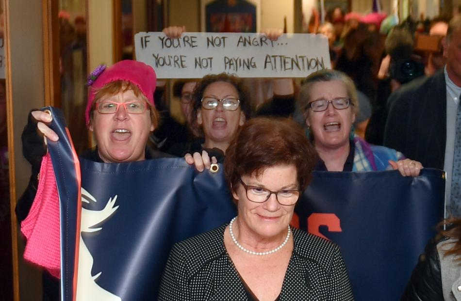SDHB commissioner Kathy Grant is hounded by protesters as she follows the Prime Minister out of Dunedin hospital. Photo: Stephen Jaquiery