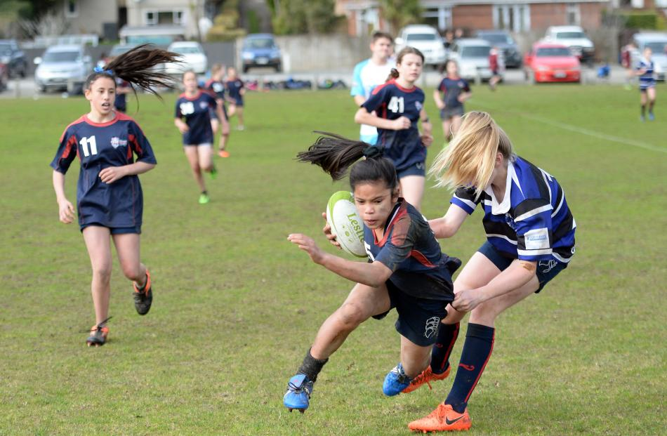 Kavanagh College's Jamaica Cabantoc (12) tries to evade the tackle of Balmacewen Intermediate's Samantha Grey (12). Photos: Linda Robertson