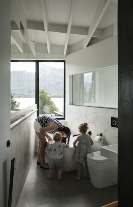 The angular bathroom squeaks between a bedroom and the kitchen void it overlooks. The window...