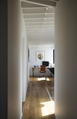 The exposed roof structure provides texture on the second level. A study nook occupies the end of...