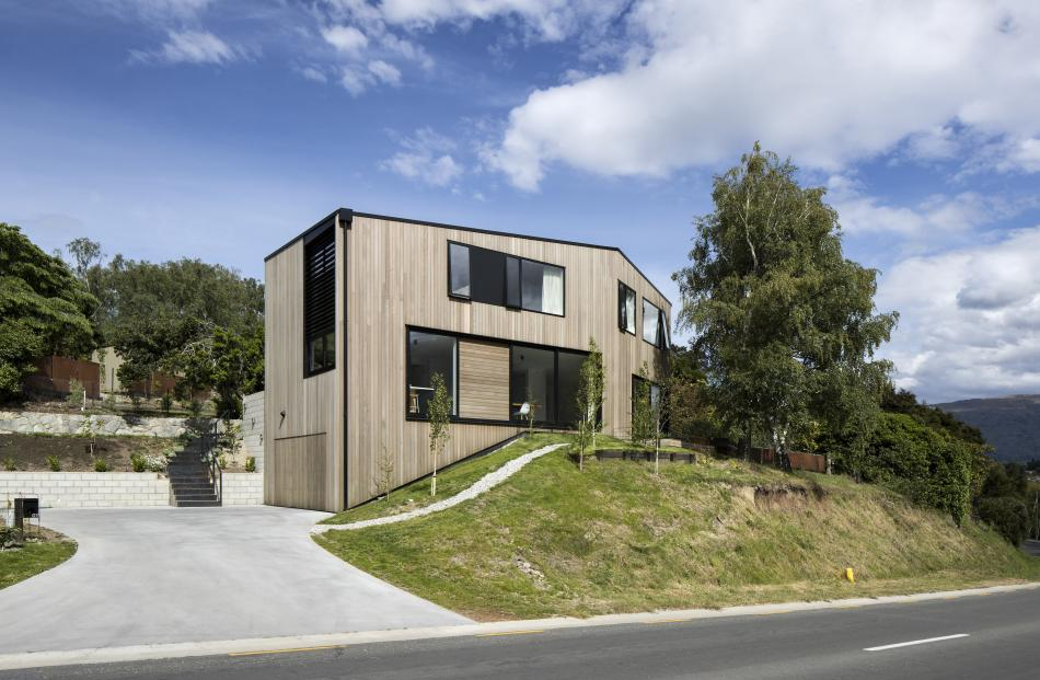 The home nestles into its sloping, corner site, tucking just under height limits. The owner's...