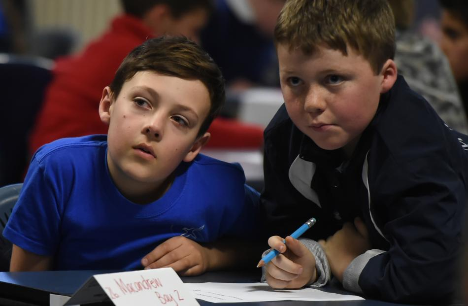 Macandrew Bay School pupils (from left) William Mooney (11) and Jackson Evans (9) listen for the...