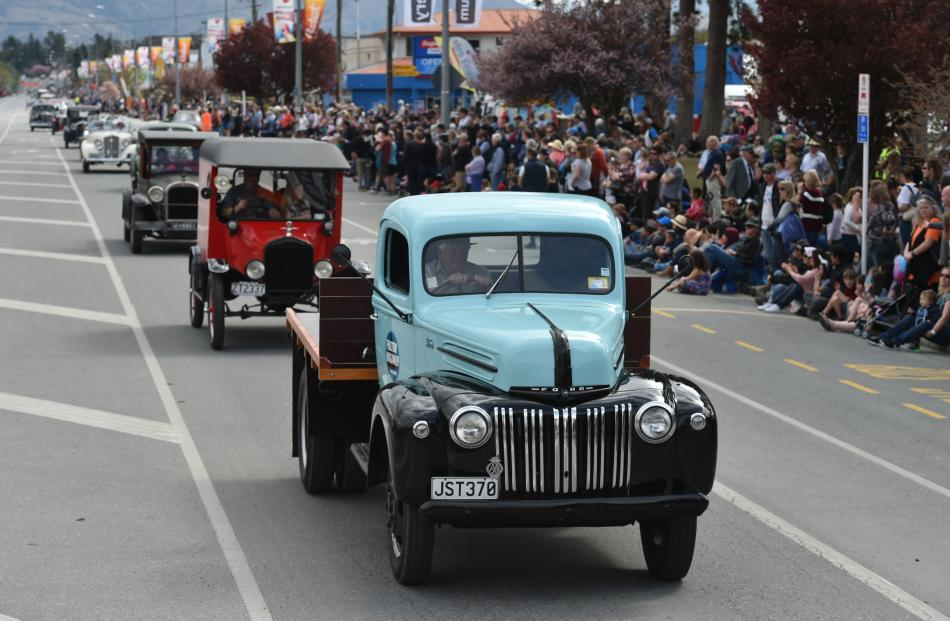 Vehicles from bygone years proceed down Centennial Ave on Saturday.