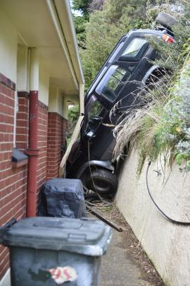 An SUV sits wedged between a bank and a house in Stuart St after it crashed down a bank early yesterday.