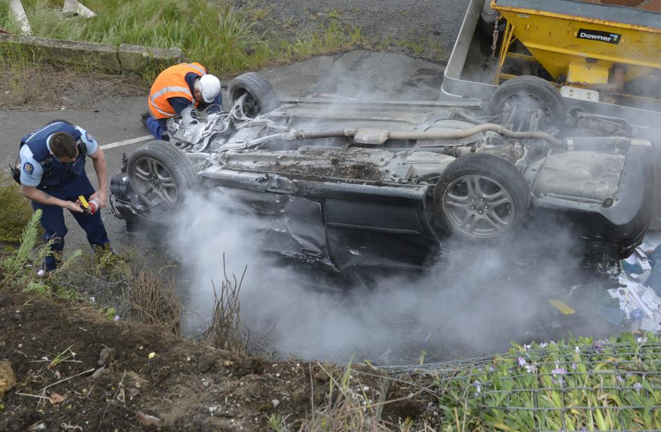 A police officer tries to extinguish a smoking car following a crash on Main South Rd in Green...