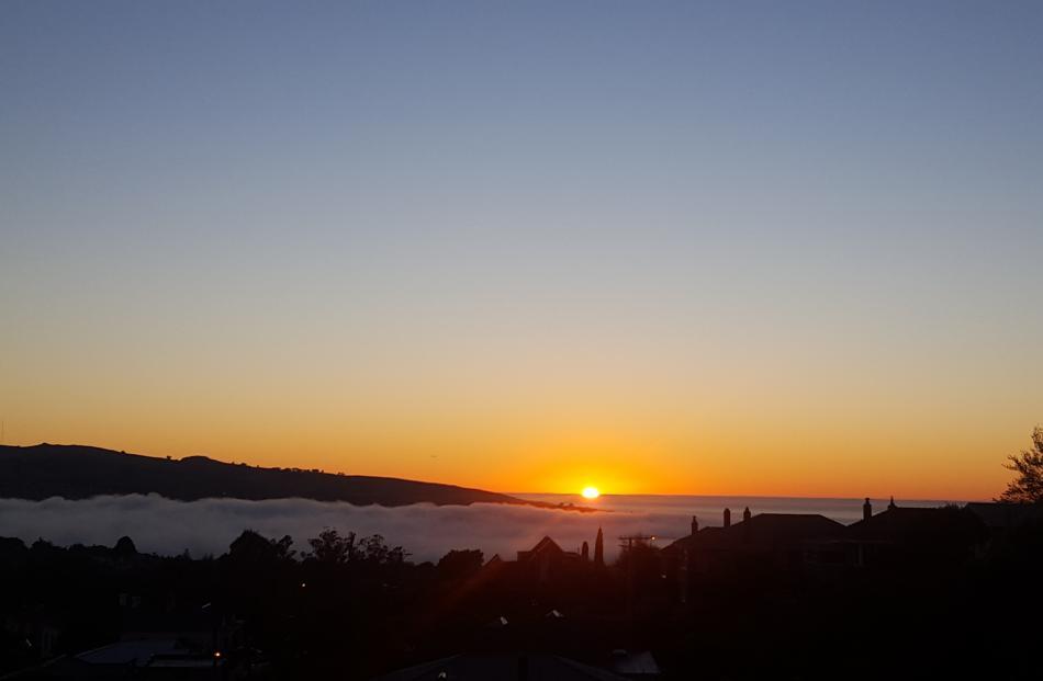 Golden sunrise hovers above Dunedin fog. Photo: David Loughrey