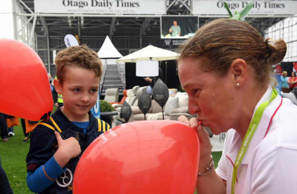 Isaac Wallace (5), of Dunedin, looks on as Charlotte Ireland, of Mike Pero Mortgages, blows up...