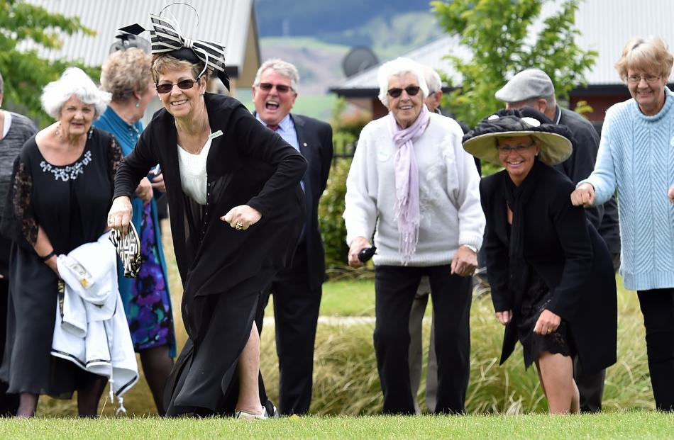 Glengarry Court Melbourne Cup party organiser Jennifer Milburn (front) leads party-goers during the 2017 Wingatui Melbourne Cup race day.