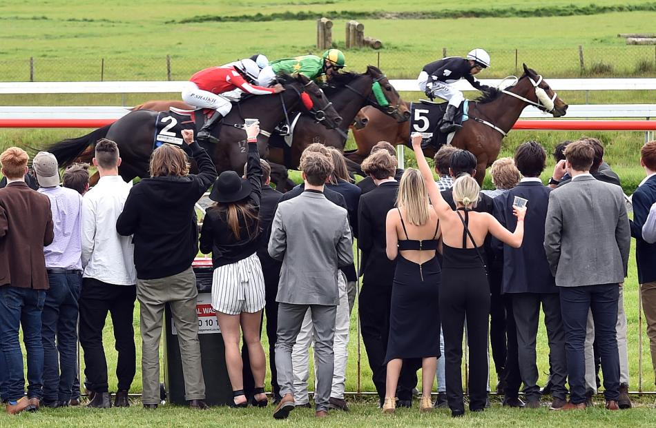 A group of punters gather to watch the finish of race 5 at Wingatui yesterday.