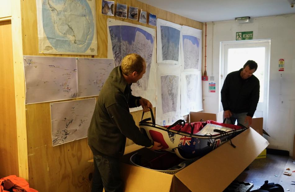 Jean Burgun (left) helps Mark Sedon pack his pulk (sled), featuring a New Zealand flag.