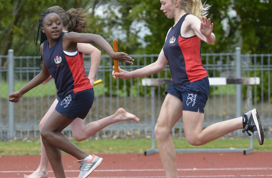 Samantha Grey (right, 12) passes the baton to Elizabeth Olusina (12) for Balmacewen Intermediate...