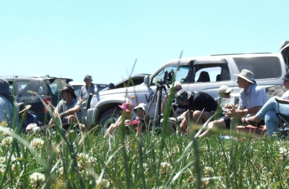 Attendees listen to speakers at a field day at Matakanui Station in a paddock showing the...