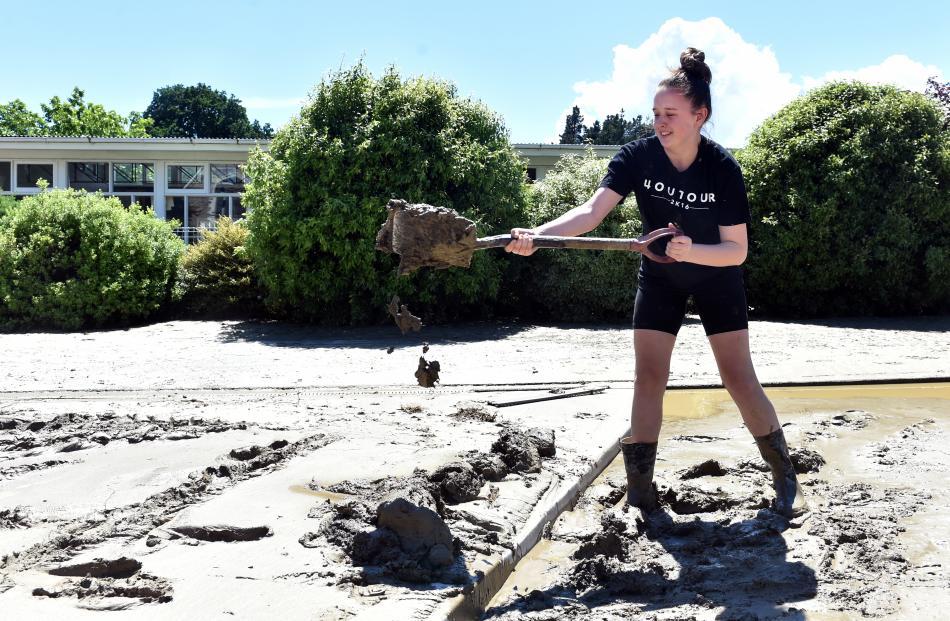Roxburgh Area School pupil Caitlin Richards (16) digs silt and muck after the flood. Photos: Peter McIntosh