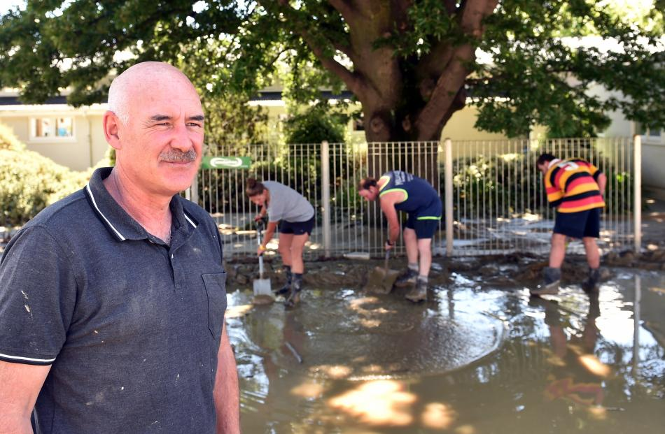 Helpers clear water and mud from outside the Roxburgh Area School watched by principal Gary Pasco.