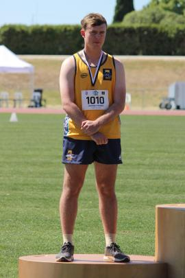 Hamish Mears (16) accepts the senior boys shotput bronze medal.