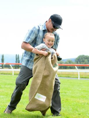 Ian Hutton of Palmerston North helps his son Leroy Hutton (4) to finish the sack race at The Interislander Summer Festival at Wingatui Racecourse on Boxing Day. PHOTOS: LINDA ROBERTSON.