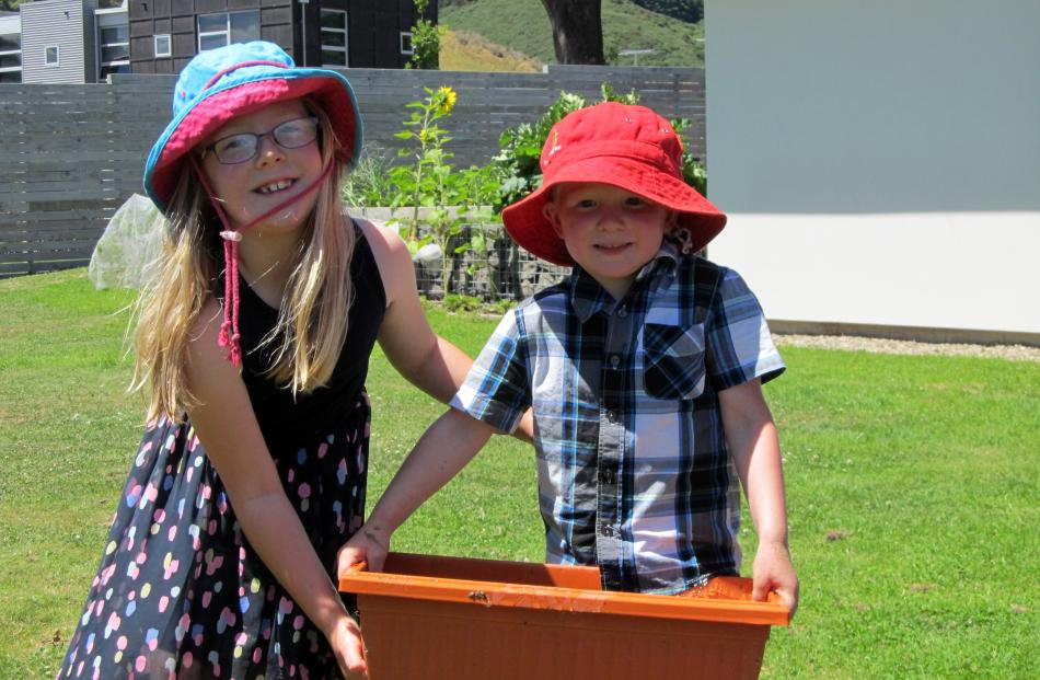 Brooke (6) has her finger in the drainage hole so James (4) Loughrey can get most of the water to the sandpit. Photo: Raewyn Loughrey