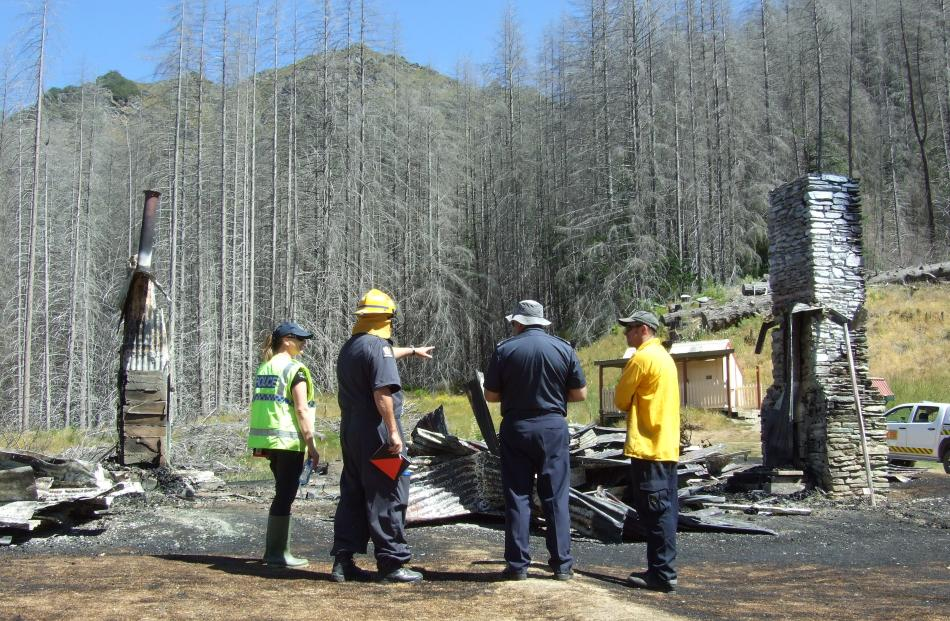 Detectives and Fire and Emergency New Zealand officers examine the remains of Mount Aurum...