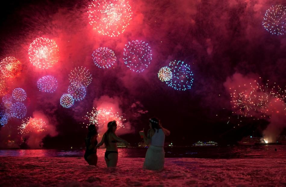 People watch as fireworks explode over Copacabana beach during New Year celebrations in Rio de...