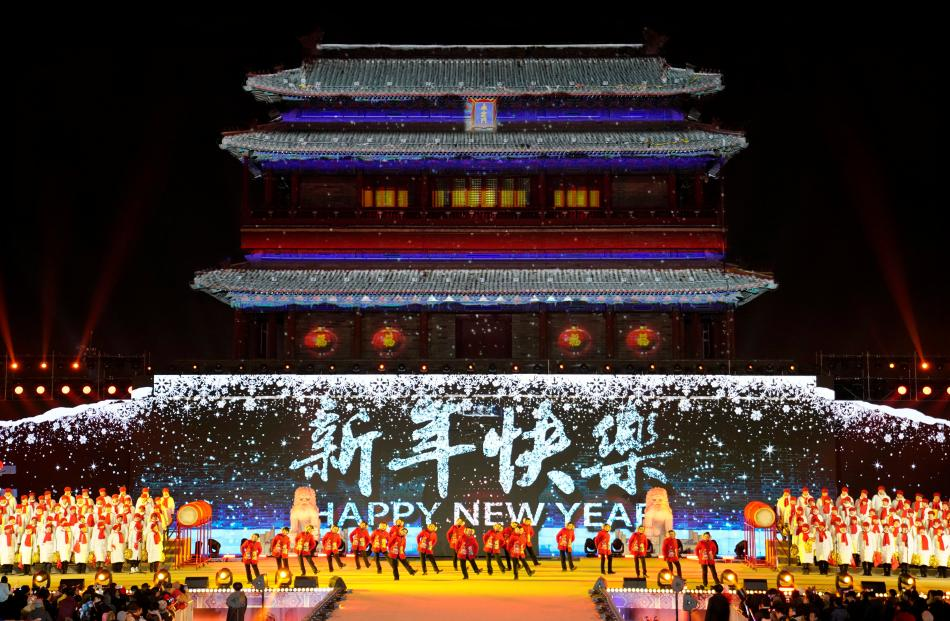 People dance to celebrate the new year during a countdown event at Yongdingmen Gate in Beijing....