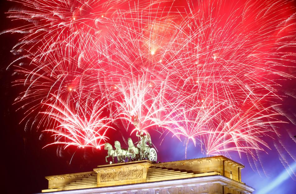 Fireworks explode next to the Quadriga sculpture atop the Brandenburg gate during New Year...