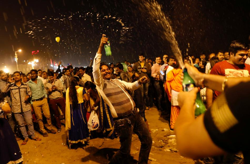 People dance during the New Year's celebrations on a beach in Mumbai, India. Photo: Reuters