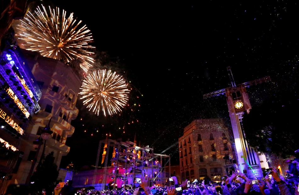 People watch fireworks in the rain on New Year's Day in downtown Beirut, Lebanon. Photo: Reuters