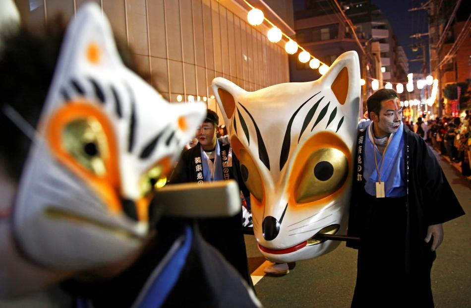 Participants dressed up as foxes prepare for the parade for the first prayer of the New Year in...
