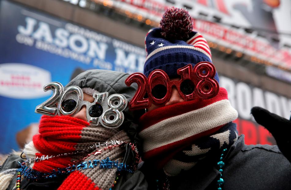 Revelers gather in Times Square as a cold weather front hits the region ahead of New Year's...