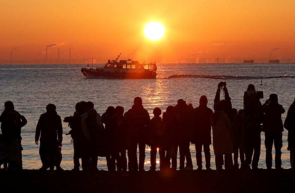 People watch the first sunrise on New Year's Day at a beach in Tokyo, Japan. Photo: Reuters