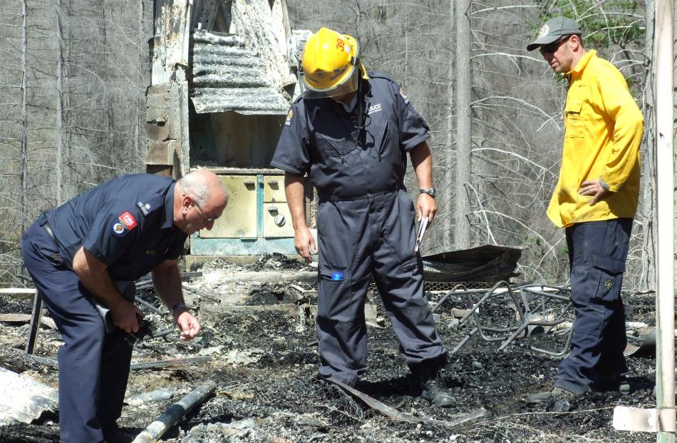 Fire and Emergency New Zealand officers and a police detective examine the scene of the Mount Aurum Homestead fire yesterday.