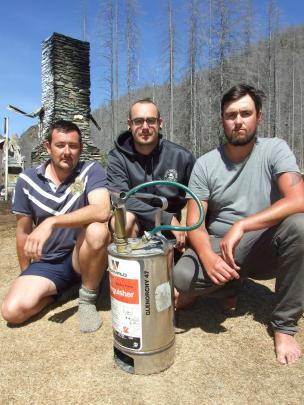 Queenstown friends (from left) Lee Gamble, Alan Wharton and Morgan Harteveld with one of the hand-pumped fire extinguishers they used to try to put out the fire which destroyed the historic Mount Aurum Homestead at the Skippers camping area near Queenstow