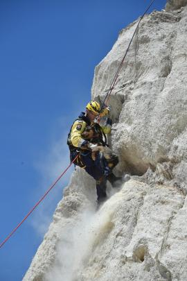 Cromwell firefighter Rowen Dunnet clings to Bowie after abseiling down a cliff (right) to rescue the 2-year-old huntaway at the historic diggings in St Bathans on New Year's Day.