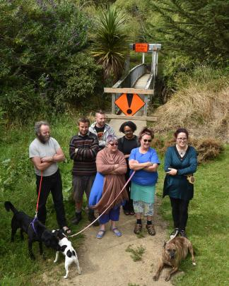 Standing by a flood-damaged and closed suspension footbridge over the Waitati River last week are Waitati residents (front, from left) Gerry Thompson, with Labrador Onyx, Hayden McLean, Louise Booth, Therese Hailes with Jack Russell Tutu, Fleur Sculpher w