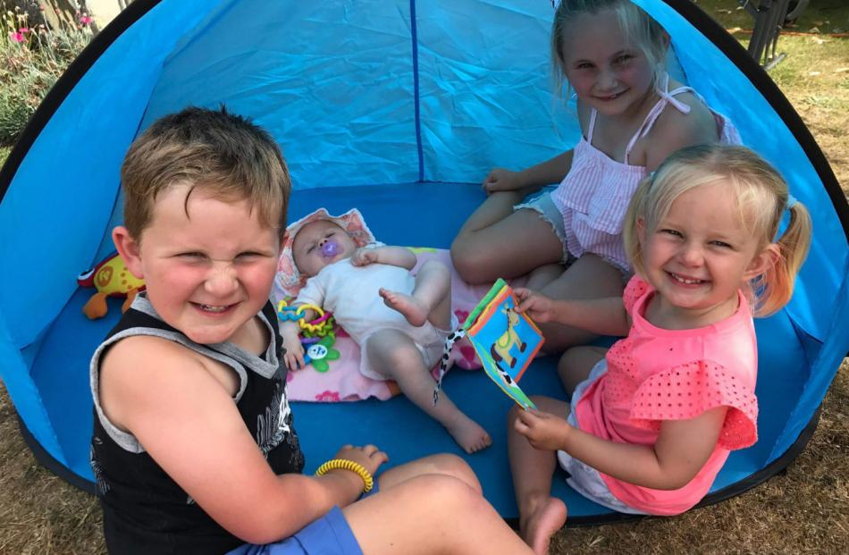Cousins Liam Foley (5), Florence Harris (5 months), Annabelle Foley (7) and Payton McElrea (3) take cover from the sun at Lake Manapouri on New Year's Eve. Photo: Jamie McElrea