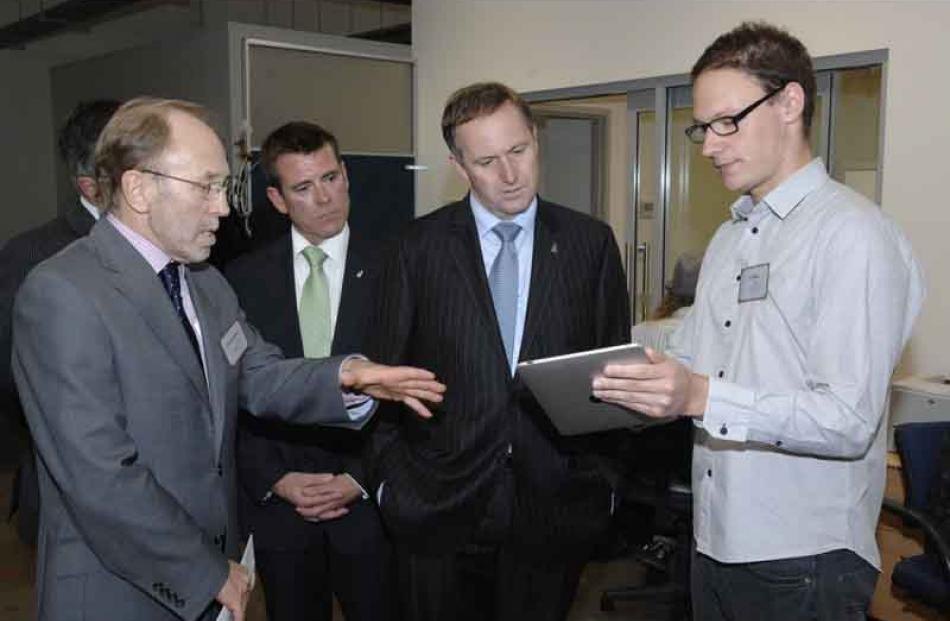 "Games developer Tim Nixon (right) shows PM John Key the game ""Flutter"" watched by NHNZ managing..."