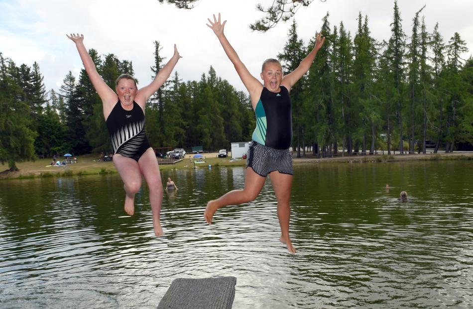 Madison Lobb (11) and Sophie Potter (13), both from Dunedin, leap from the diving board at the Naseby dam.