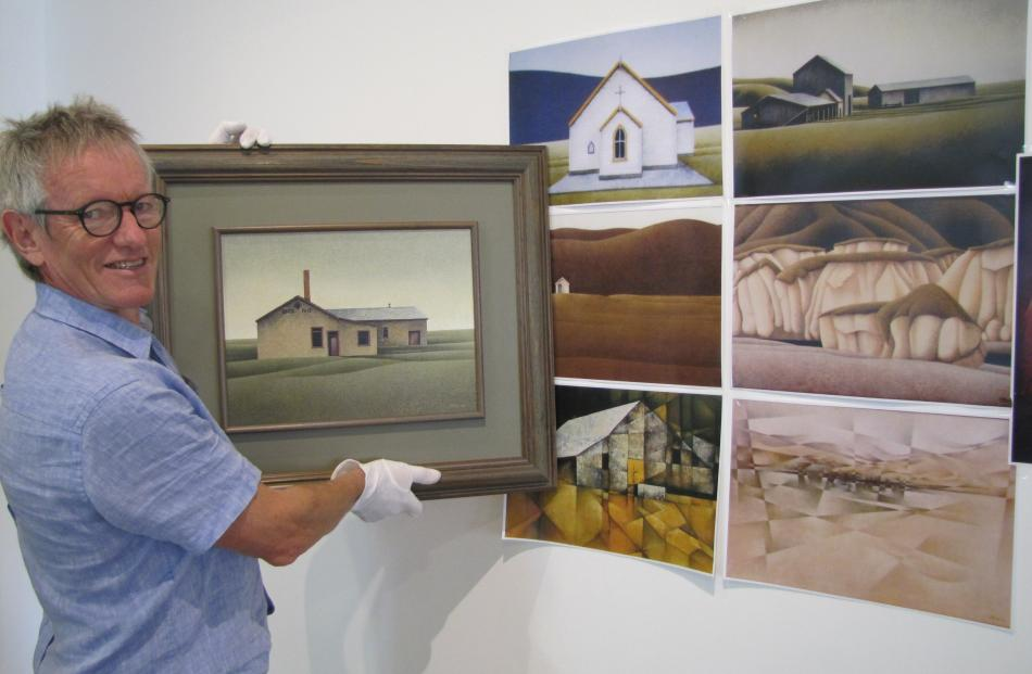 Central Stories Museum and Art Gallery general manager Maurice Watson holds a painting by the late Elizabeth Stevens. Behind are images of other paintings by Stevens being sought for an upcoming exhibition of the Central Otago artist's works. Photo: Pam J