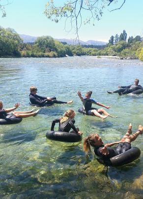 Floating on tyre tubes on the Hawea River on December 27 are (from left) Ruby  (12) and  Danyon ...