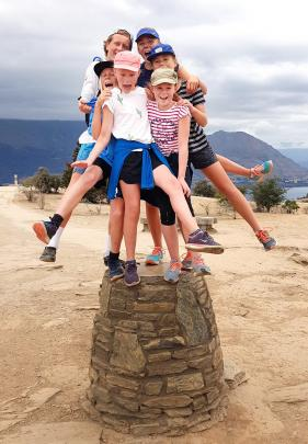 Six cousins balanced on the stone cairn at the top of Mt Iron in  Wanaka on January 10  are (from...