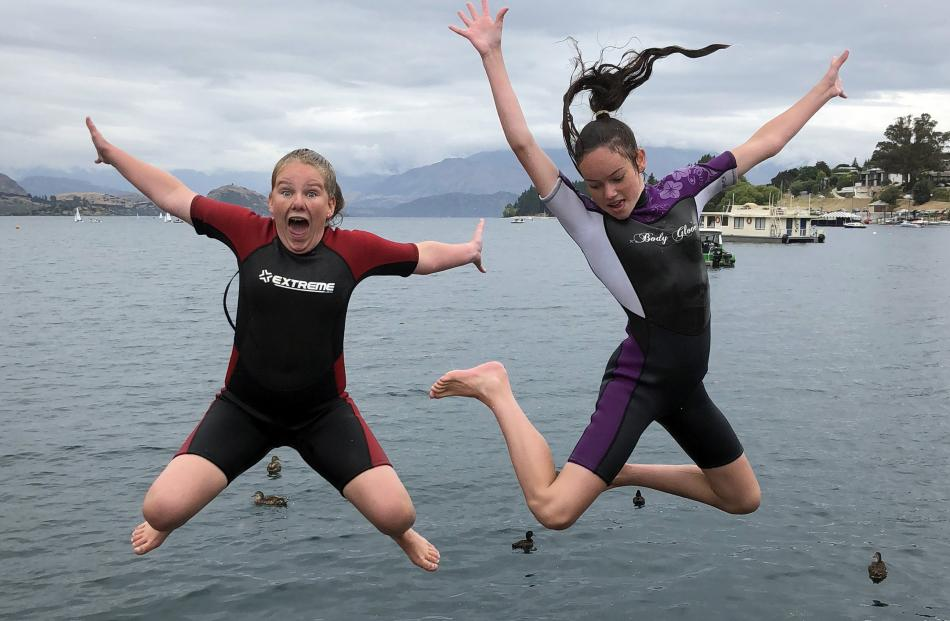 Lucie Cummings (13) and Alyssa May (11) of Lawrence, jump off the wharf at the Wanaka foreshore...