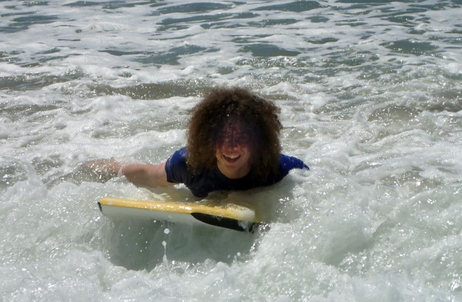 Murray Powell (17) is  full of joy at surfing in the foamy waves of Long Beach on Tuesday. Photo:...