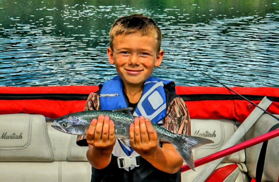Riley Gill (8), of Cromwell, shows off his very first salmon caught at Lake Dunstan two days...